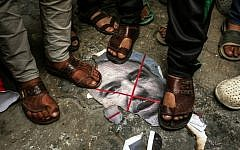 Palestinians step on a burnt image of Defense Minister Avigdor Lieberman in front of the house Hamas chief Ismail Haniyeh's home in Gaza on November 14, 2018. (Mahmud Hams/AFP)
