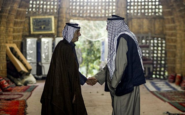Members of an Iraqi clan shake hands as they meet inside a straw tent in the town of Mishkhab, south of Najaf on November 15, 2018. (Haidar Hamdani/AFP)