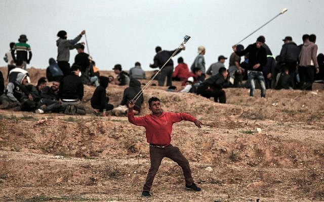 A Palestinian demonstrator uses a slingshot to throw stones towards Israeli forces during a protest on November 16, 2018, on the eastern outskirts of Gaza City, near the border with Israel. (Mahmud Hams/AFP)