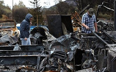 Noah Fisher (R) and Dusty Cope (L)  look through the remains of their home that was destroyed by the Camp Fire in Paradise, California, on November 22, 2018. (JUSTIN SULLIVAN / GETTY IMAGES NORTH AMERICA / AFP)