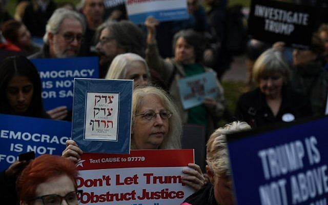 "Protesters gather at a Nobody Is Above the Law rally protesting President Trump's interference in the Mueller investigation on November 08, 2018 in Washington, DC. The Hebrew sign reads ""Justice, justice you shall pursue.""  (Larry French/Getty Images for MoveOn/AFP)"