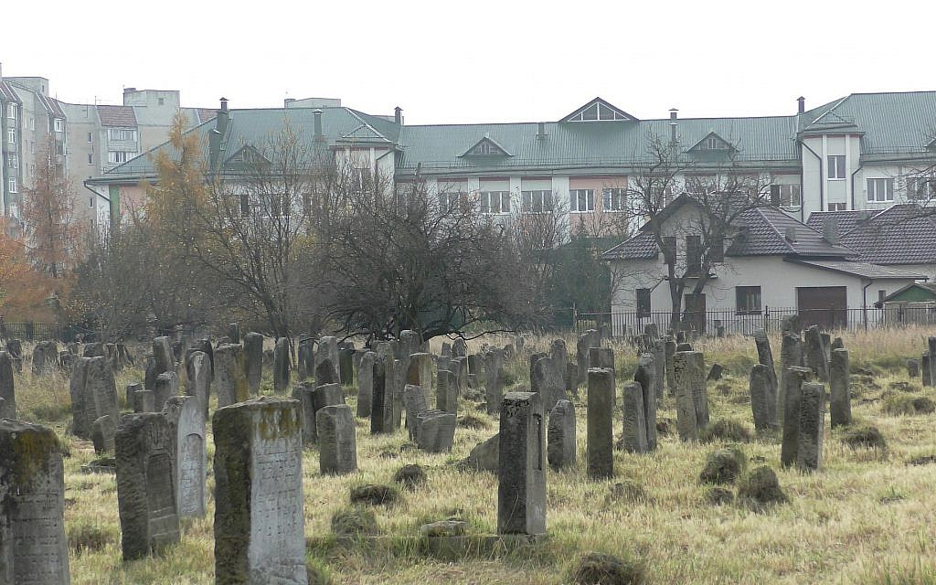 The Kalush Jewish cemetery with the Kalush Gymnasium in the background. (Bernard Dichek/ Times of Israel)