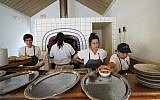 Chef de cuisine Cara Peterson, left, sous chef Julia Henner, second right, and line cook Naomi Martinez, right, work at the pita oven in Alon Shaya's restaurant Saba in New Orleans, August 23, 2018. (Gerald Herbert/AP)