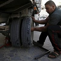 In this October 30, 2018 photo, a man removes damaged tires at a workshop in Gaza City. (AP Photo/Adel Hana)