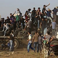In this September 21, 2018 file photo, protesters arrive on a truck with tires to burn near the the fence of Gaza Strip border with Israel during a protest. (AP Photo/Adel Hana, File)