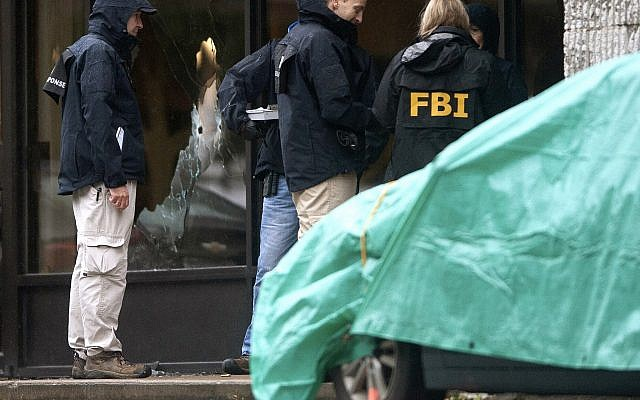 In this Saturday, Oct. 27, 2018, file photo, bullet holes can be seen in a shattered window as FBI and other law enforcement investigate the scene of a deadly shooting at the Tree of Life synagogue on in the Squirrel Hill section of Pittsburgh. (Andrew Stein/Pittsburgh Post-Gazette via AP, File)