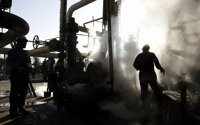 In this photo from November 17, 2007, a worker repairs a part of a unit of the Tehran oil refinery, in Tehran, Iran. (AP Photo/Vahid Salemi, File)