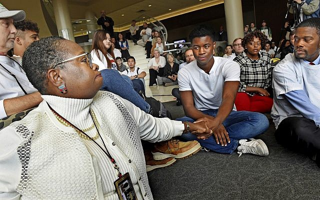 Aura Wharton-Beck, left, an assistant professor in the School of Education at the University of St. Thomas and a graduate of the school, clasps hands with Kevyn Perkins, center, during a moment of silence before a protest in the Anderson Student Center at the University of St. Thomas in St. Paul, Minnesota, October 25, 2018. (Jean Pieri/ Pioneer Press via AP)