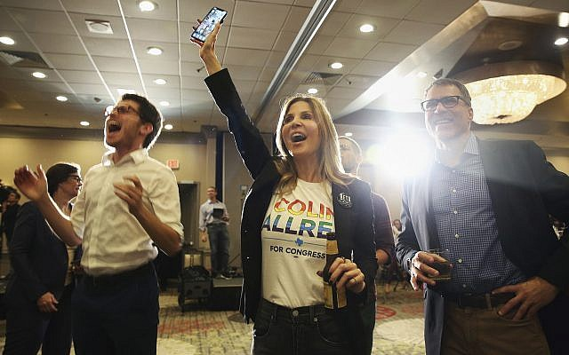 David Rosen, from left, Jennifer Karol and her husband Tom Karol react to an update on the 32nd Texas congressional race during an election night party for Democratic candidate Colin Allred at the Magnolia Hotel Dallas Park Cities in Dallas, Tuesday, Nov. 6, 2018. (AP Photo/Andy Jacobsohn)