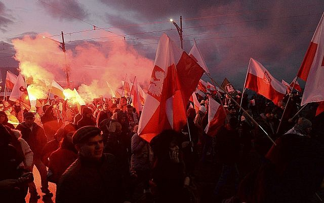 In this photo from November 11, 2017, demonstrators burn flares and wave Polish flags during the annual march to commemorate Poland's National Independence Day in Warsaw, Poland. (AP Photo/Czarek Sokolowski)