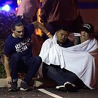 People comfort each other as they sit near the scene Thursday, November 8, 2018, in Thousand Oaks, Calif. where a gunman opened fire Wednesday inside a country dance bar crowded with hundreds of people. (AP/Mark J. Terrill)