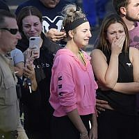 People cry as a law enforcement motorcade escorts the body of Ventura County Sheriff's Department Sgt. Ron Helus from the Los Robles Regional Medical Center Thursday, Nov. 8, 2018, in Thousand Oaks, Calif., after a gunman opened fire Wednesday evening inside a country music bar, killing multiple people including Helus. (AP Photo/Mark J. Terrill)