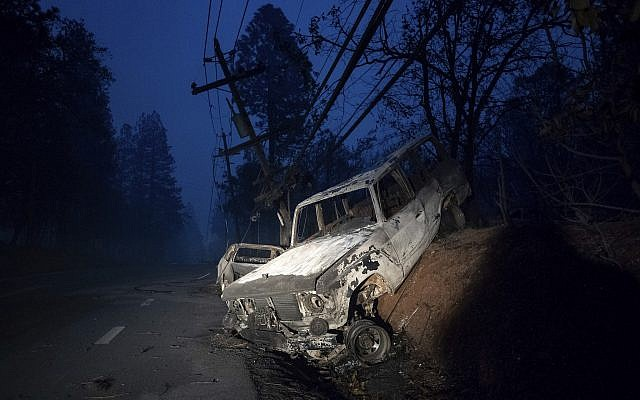 A scorched vehicle rests on a roadside as the Camp Fire tears through Paradise, Calif., on Thursday, Nov. 8, 2018.  (AP Photo/Noah Berger)