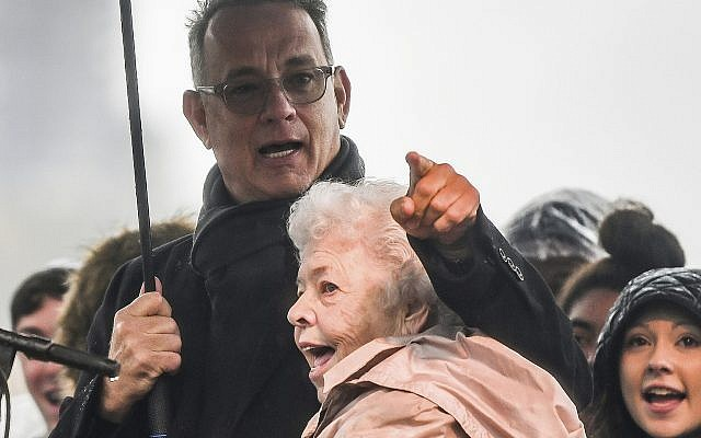 """Actor Tom Hanks embraces Joanne Rogers, the late wife of Fred Rogers, as they sing the theme song of """"Mister Rogers' Neighborhood"""" alongside a choir during the Rally for Peace and Tree of Life Victims, Friday, Nov. 9, 2018, at Point State Park in downtown Pittsburgh. (Alexandra Wimley/Pittsburgh Post-Gazette via AP)"""