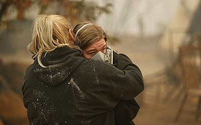 Krystin Harvey, left, comforts her daughter Araya Cipollini at the remains of their home burned in the Camp Fire, Saturday, Nov. 10, 2018, in Paradise, California. (AP/John Locher)