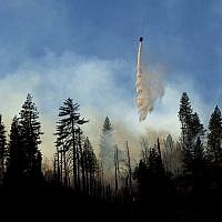 A helicopter drops water while battling the Camp Fire burning near Pulga, Calif., on Sunday, Nov. 11, 2018. (AP Photo/Noah Berger)