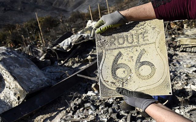 Donna Phillips shows a charred Route 66 sign she found among the possessions of her friend Marsha Maus, Sunday, November 11, 2018, after wildfires tore through the Seminole Springs Mobile Home Park in Agoura Hills, Calif. Maus has been a resident of the neighborhood for 15 years. (AP Photo/Chris Pizzello)