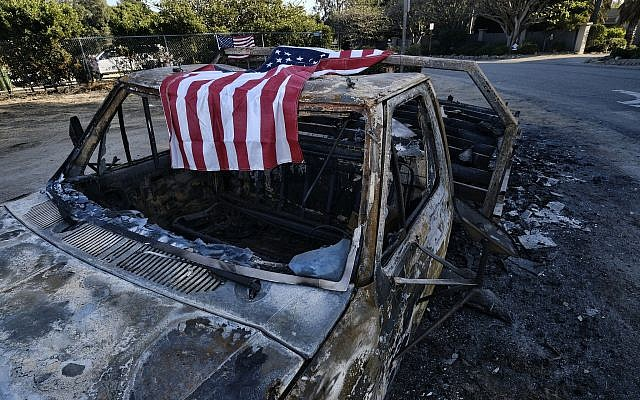 An American flag is draped over the charred remains of an old pickup truck entering Point Dume along the pacific coast highway in Malibu, California, on November 11, 2018. (AP Photo/Richard Vogel)