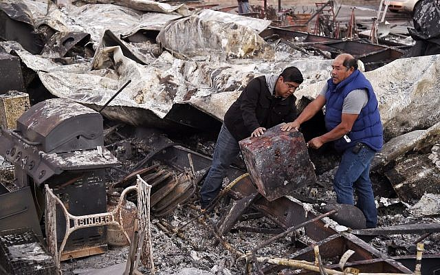 Santos Alvarado, right, and his son Ricky recover a safe deposit box from their destroyed home at Seminole Springs Mobile Home Park, November 11, 2018, following devastating wildfires in the area in Agoura Hills, California. (AP Photo/Chris Pizzello)