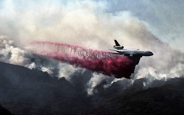 A firefighting DC-10 makes a fire retardant drop over a wildfire in the mountains near Malibu Canyon Road in Malibu, California, on November 11, 2018. (AP Photo/Richard Vogel)