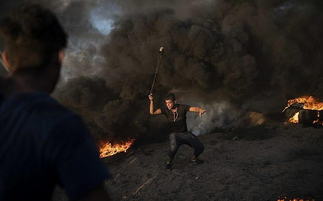 In this September 7, 2018 photo, a Palestinian protester hurls stones during a protest at Gaza Strip's border with Israel, east of Gaza City. (AP Photo/Felipe Dana)