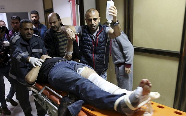 Colleagues wheel AP cameraman Rashed Rashid, 47, into a treatment room in Beit Lahiya in the northern Gaza Strip after he is shot in his left leg while covering a protest on the beach, November 19, 2018. (AP Photo/ Adel Hana)