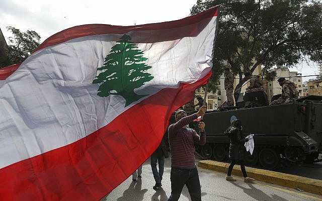 A protester waves a Lebanese flag during a protest against corruption and the failure of long-serving politicians to form a government, in Beirut, Lebanon, Thursday, Nov. 22, 2018. Lebanon is marking 75 years of independence with a military parade Thursday in Beirut, but many anxious Lebanese feel they have little to celebrate: the country's corruption-plagued economy is dangerously close to collapse and political bickering over shares in a new Cabinet is threatening to scuttle pledges worth $11 billion by international donors. (AP Photo/Hussein Malla)