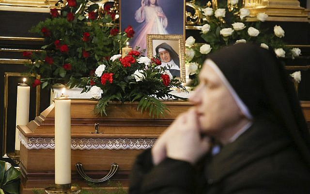 A nun prays beside the casket and photo of 110-year-old Roman Catholic Sister Cecylia Roszak, believed to be the world's oldest nun, and a rescuer of Jews during the Holocaust, during her funeral ceremonies at Church of Our Lady of the Snows the Dominican in Krakow, Poland, November 22, 2018. (AP Photo/Beata Zawrzel)