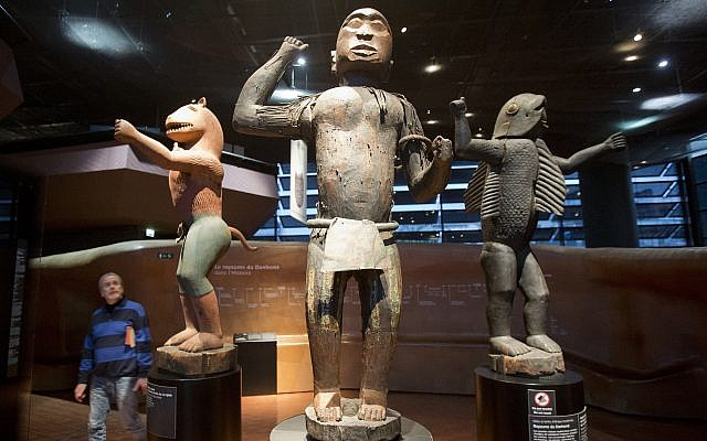 Visitors look at wooden royal statues of the Dahomey kingdom, dated 19th century, today's Benin, at Quai Branly museum in Paris, France, Friday, Nov. 23, 2018 (AP/Michel Euler)