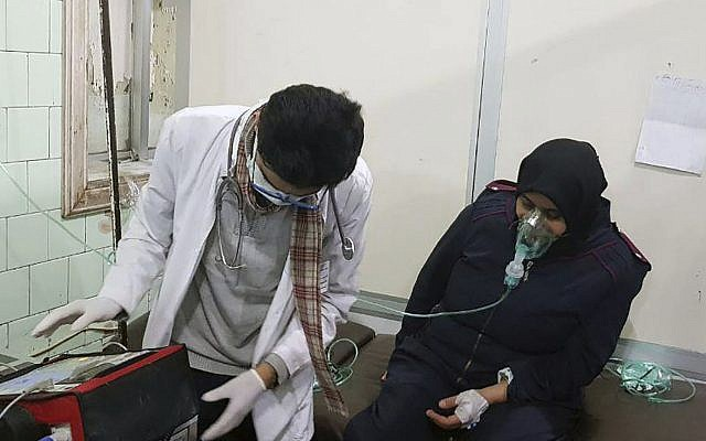 This photo released by the Syrian official news agency SANA shows a woman receiving oxygen through respirators following a suspected chemical attack on her town of al-Khalidiya, in Aleppo, Syria, Saturday, Nov. 24, 2018. (SANA via AP)