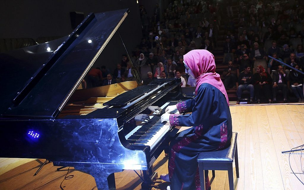 Palestinian pianist Yara Thabit plays the piano during a concert to mark the debut of Gaza's only grand piano after it was rescued from conflict, at a theater nestled in the Palestinian Red Crescent Society's building in Gaza City on Nov. 25, 2018. (AP Photo/Adel Hana)