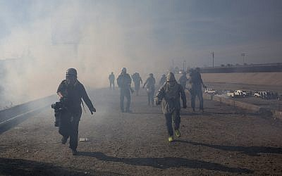 Migrants run from tear gas launched by US agents on the Mexico-US border, November 25, 2018. (AP Photo/Rodrigo Abd)