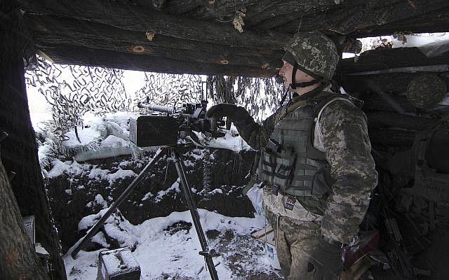 A Ukraine army soldier stands on duty with his heavy machine gun at an undisclosed location in eastern Ukraine, November 26, 2018. (Alexander Shulman/AP)