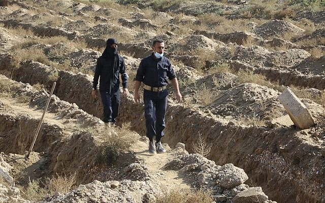 This frame grab from a video provided on Thursday, November 22, 2018, shows Syrian workers in Raqqa walk on a mass grave believed to contain the bodies of many hundreds of civilians and Islamic State fighters in Raqqa. (AP Photo)