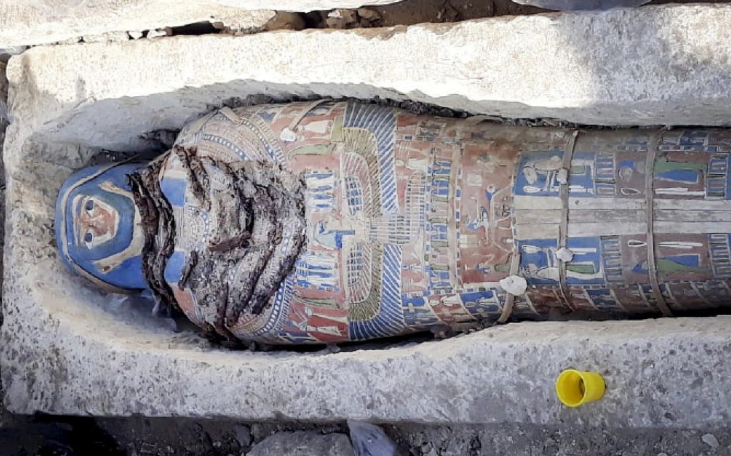 This undated photo released by the Egyptian Ministry of Antiquities on Wednesday, Nov. 28, 2018, shows an ancient mummy covered with a layer of painted cartonnage, which was found inside a sarcophagus in area of King Amenemhat II's pyramid in the Dahshur royal necropolis, about 25 miles south of Cairo. Egypt says archaeologists have discovered eight limestone sarcophagi with mummies inside. (Egyptian Ministry of Antiquities via AP)