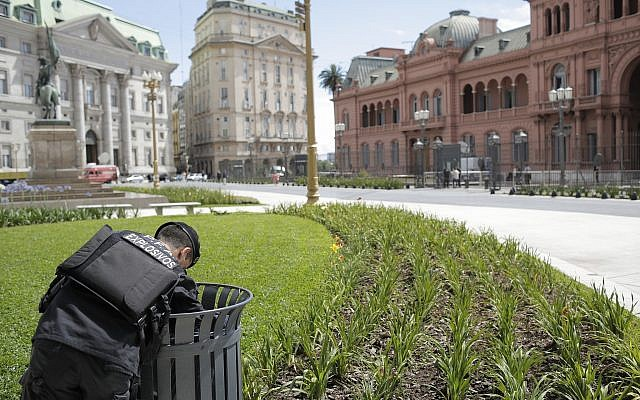 An anti-explosives police officer inspects a garbage bin in front of the presidential palace in Buenos Aires, Argentina, on November 29, 2018. (AP Photo/Sebastian Pani)