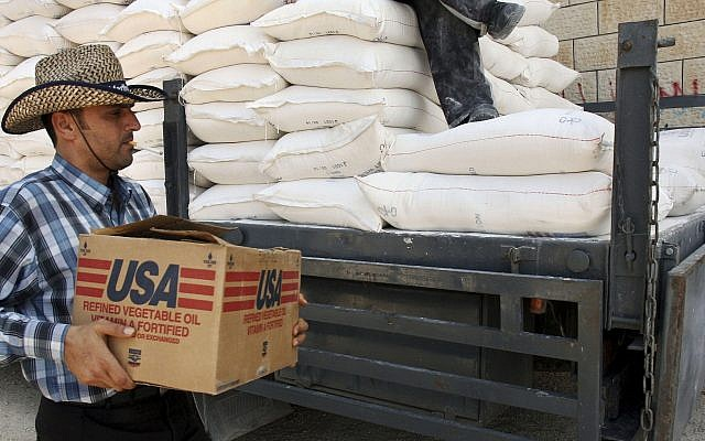 A Palestinian carries a box of vegetable oil as he walks past bags of flour on a truck donated by USAID, or the United States Agency for International Development, at a depot in the West Bank village of Anin near Jenin, June 4, 2008 (AP Photo/Mohammed Ballas)