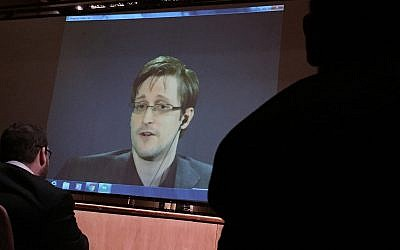 In this Feb, 17, 2016 file photo, former National Security Agency contractor Edward Snowden, center speaks via video conference to people in the Johns Hopkins University auditorium, in Baltimore. G(AP Photo/Juliet Linderman, File)
