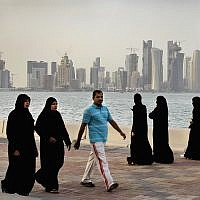 In this Saturday, April 7, 2012 file photo, the new high-rise buildings of downtown Doha, photographed in the background as Qatari women and a man walk by the sea in Doha, Qatar. (AP/Kamran Jebreili)