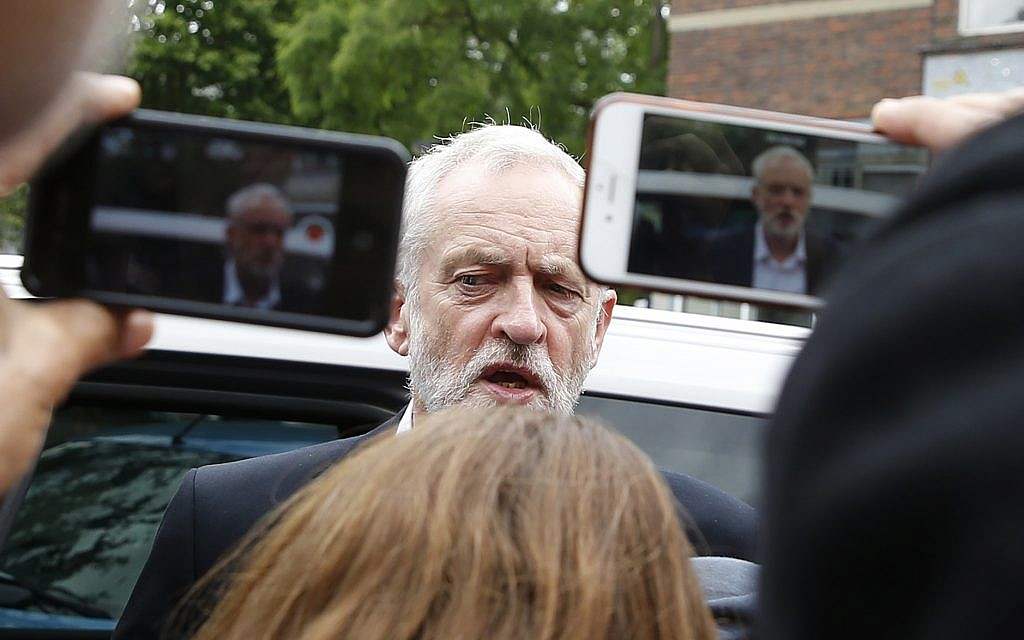 People take photos of Britain's Labour Party leader Jeremy Corbyn during a visit to the scene of the massive fire in Grenfell Tower, in rear, in London, Thursday, June 15, 2017. (AP/Alastair Grant)