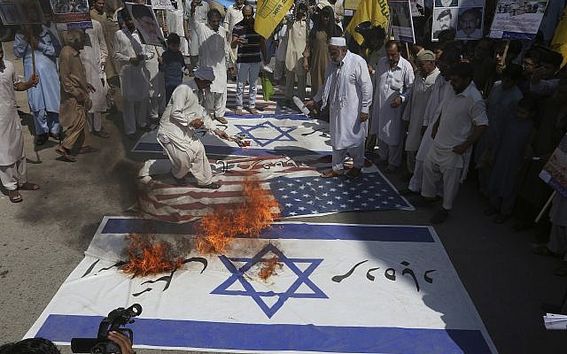 Shiite Muslims burn representation of Israeli and US flags during a rally to mark Al-Quds (Jerusalem) Day in Peshawar, Pakistan, Friday, June 23, 2017. (AP Photo/Muhammad Sajjad)