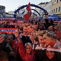 Supporters of the Austrian Freedom Party FPOe hold scarves and pictures of party leader Hans-Christian Strache and last year's presidential candidate Norbert Hofer during the final campaign rally of the party in Vienna, Austria, Friday, Oct. 13, 2017. (AP/Matthias Schrader)