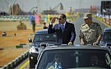 In this photo provided by Egypt's state news agency, MENA, Egyptian President Abdel-Fattah el-Sissi salutes as he inspects troops with Minister of Defense Sedki Sobhy, in the Red Sea port city of Suez, Egypt, Sunday, Oct. 29, 2017. (MENA via AP)