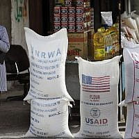 A Palestinian pupil walks past United Nations Relief and Works Agency, (UNRWA) and USAID humanitarian aid, on June 6, 2010 in the Shatie refugee camp in Gaza City. (AP Photo/Lefteris Pitarakis, File)