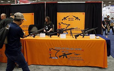 In this May 4, 2018, file photo, attendees walk by a display of AR-15's and AR-10's at the National Rifle Association convention in Dallas. (AP/Sue Ogrocki)