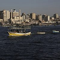 Palestinian fishing boats sail into the waters of the Mediterranean Sea in Gaza City, Monday, July 9, 2018, with buildings of Gaza City seen in background. (AP Photo/Adel Hana)