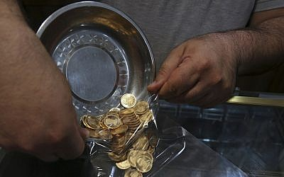 In this illustrative photo from August 12, 2018, an Iranian goldsmith counts gold coins at the sprawling Grand Bazaar in Tehran, Iran. (AP Photo/Vahid Salemi)