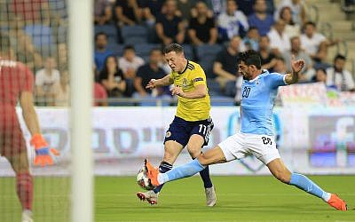 Scotland's Callum McGregor shoots by Israel's Omri Ben Harush during Nations League game in Haifa, Israel, Thursday, Oct. 11, 2018. (AP Photo/Ariel Schalit)