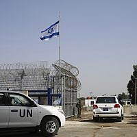 An Israeli soldier opens the border gates as a UN vehicle enters Syria at the Quneitra crossing in the Golan Heights, Monday, October 15, 2018. (AP Photo/Ariel Schalit)