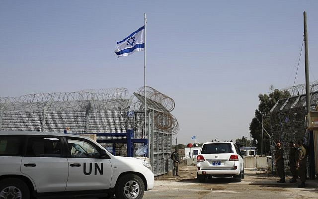 An Israeli soldier opens the border gates as a UN vehicle enters Syria at the Quneitra crossing in the Golan Heights, Monday, Oct. 15, 2018. (AP Photo/Ariel Schalit)